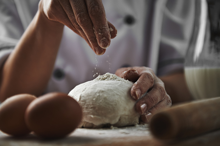 Femme dans le chef uniforme de la farine en ajoutant à la pâte à pizza préparer dans la cuisine. Cookery et le concept de la nourriture saine.