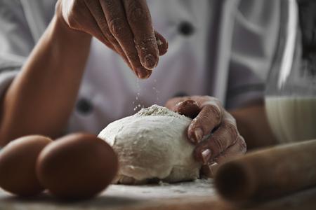 harina: Mujer en la harina añadiendo uniforme del cocinero que prepara la pasta de pizza en la cocina. La cocina y el concepto de alimentación saludable.