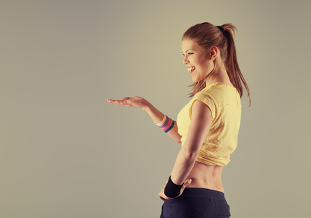jazz modern: Dancing woman showing at copy space. Young energetic fitness instructor working out in sport club.