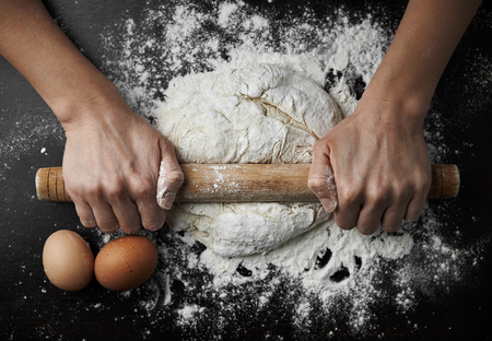 Close-up of female hands rolling dough with pin on wooden table. Concept of cooking and homemade meal. Standard-Bild