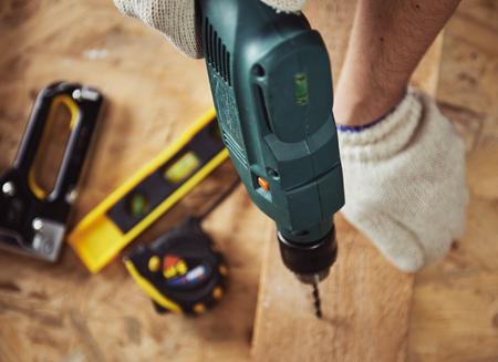 Baumeisters mit Bohrmaschine. Professionelle Schreiner mit Holz und Gebäude Werkzeuge im Haus arbeiten.