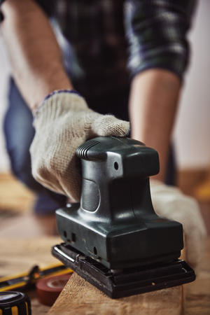 planos electricos: Male carpenter using electric planer for woodwork in joinery. Concept of DIY and furniture renovation.