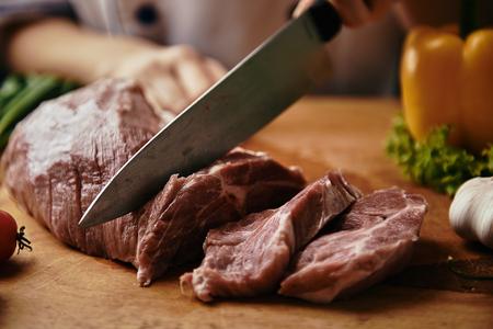 シェフの手がフライにして準備をして生肉をスライスします。ステーキとグリル メニューのコンセプトです。
