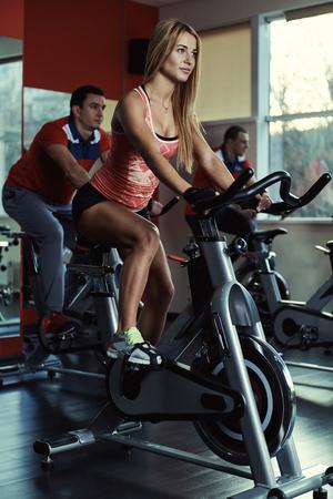 personas activas jóvenes que ejercen sobre la bicicleta en la clase de gimnasia. la gente del deporte que hace el giro entrenamiento.