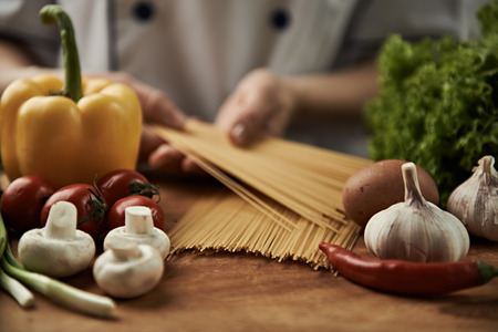 raw food: Woman chef cooking italian pasta with garlic, pepper, mushrooms, tomatoes and greens on wooden table. Stock Photo