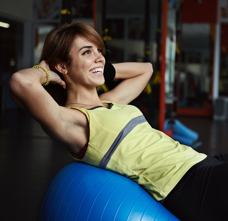 evening class: Happy young woman training abdominal muscles on fit ball in aerobics class. Body improvement and care concept. Stock Photo