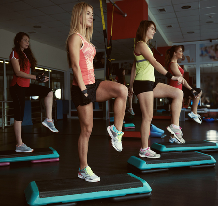 step by step: Young pretty women exercising on step boards in aerobics class. Fitness people working out with steppers in the gym. Stock Photo