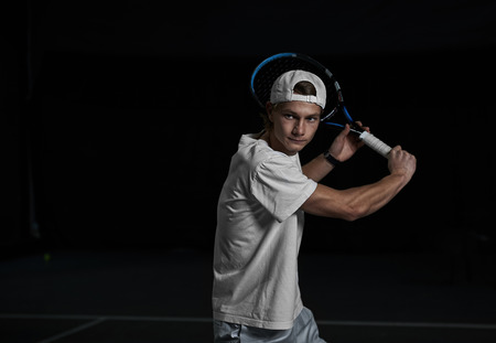 Young man tennis player holding racket ready to hit a ball. Professional sportsman coaching on tennis court.