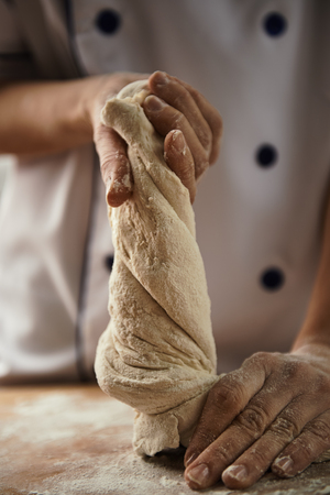 Close-up of female chef hands kneading the dough on the board. Bread preparation.