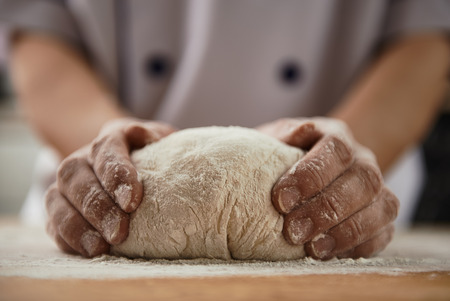 Close-up of woman baker hands kneading the dough on black board with flour powder. Concept of baking and patisserie. Stockfoto