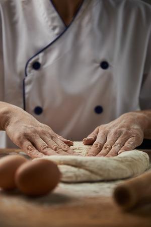 haciendo pan: panadero profesional hace la pasta de pan en la mesa de madera con ingredientes para hornear.