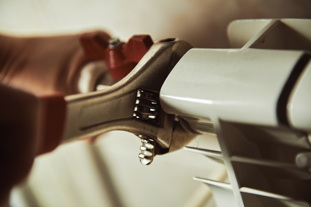 Close-up z rąk technika sprawdzania chłodnicę i ogrzewanie w domu. Koncepcja naprawy grzejnika.