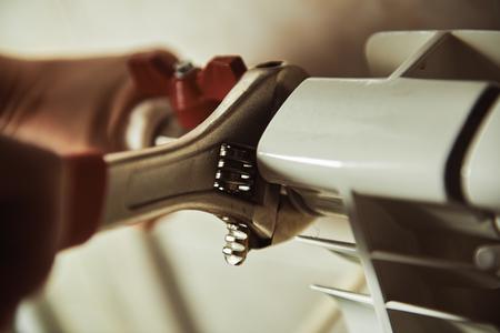fontaneria: Primer plano de las manos del técnico de comprobación del radiador y calefacción en una casa. Concepto de reparación del calentador.