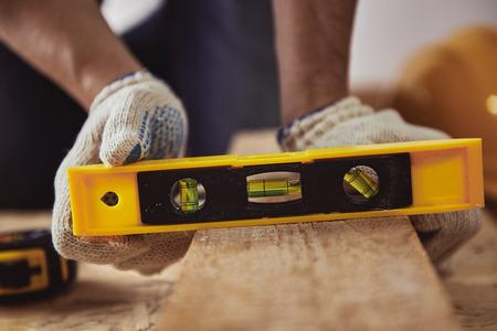 trinchante: Hombre nivel de cheques tallador de tablón de madera en su taller. Concepto de la construcción.