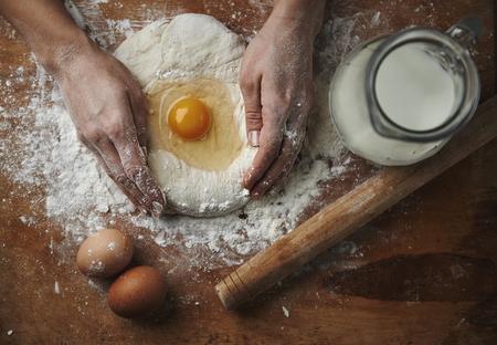 여성의 근접 촬영 계란과 소박한 부엌에서 나무 보드에 밀가루 반죽을 혼합 손.