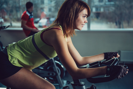 Cycling class in fitness club. Active girl training at sport equipment in the gym. Banque d'images