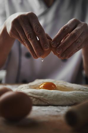 panadero: Manos de la mujer que rompe el huevo en la masa de la pasta. Ingredientes frescos. Preparación de la comida. Foto de archivo