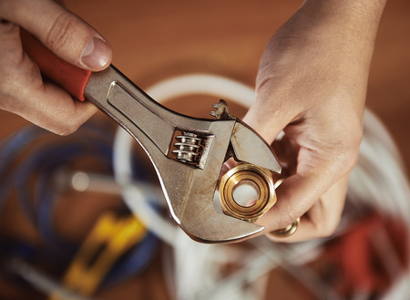 fixtures: Close-up of plumber hands screwing nut of pipe with wrench over plumbing tools background. Concept of repair and technical assistance. Stock Photo