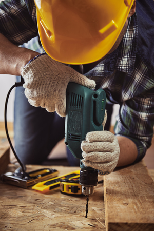 work gloves: Craftsman in helmet and gloves holding drill at work. Male contractor woodworking with building tools.