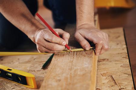 pravítko: Řemeslník měření dřevěnou fošnu s pravítkem na podlaze. Koncept kutilství, zpracování dřeva a domácí renovace. Reklamní fotografie