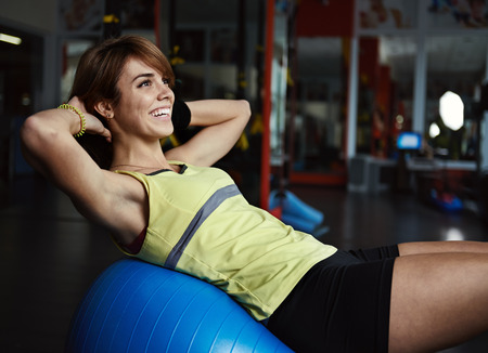 aerobics class: Happy young woman training abdominal muscles on fit ball in aerobics class. Body improvement and care concept. Stock Photo