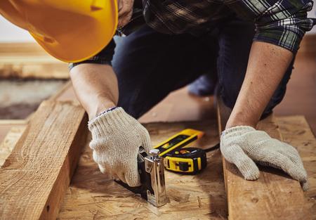 albañil: Constructor del hombre joven en ropa de trabajo reparación de muebles de madera en una casa. Concepto de actualización y carpintería.