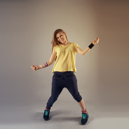 Fitness dance exercise at studio. Portrait of young cheerful girl training zumba.