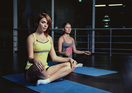 shaping: Two concentrated women sitting on mats in lotus position practicing yoga in gym. Concept of recreation and lifestyle. Stock Photo