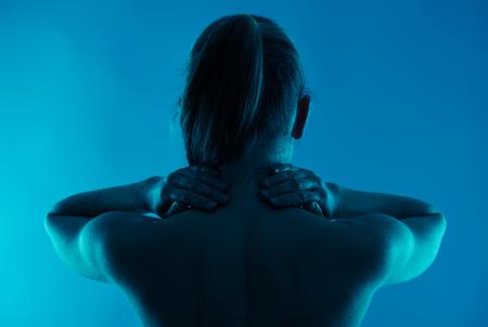 Blessure au dos. massage du cou. Jeune femme souffrant de la maladie de la colonne vertébrale.