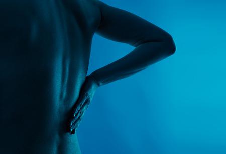 dolor de espalda: El dolor de espalda y el lomo. persona joven que sufre de osteoporosis. La asistencia sanitaria y médica.