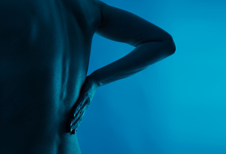Zad a bederní bolest. Mladý člověk trpící osteoporózou. Zdravotní péče a lékařské. Reklamní fotografie