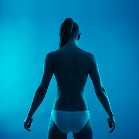 coccyx: Back treatment and therapy. Shirtless female with healthy spine over blue background.