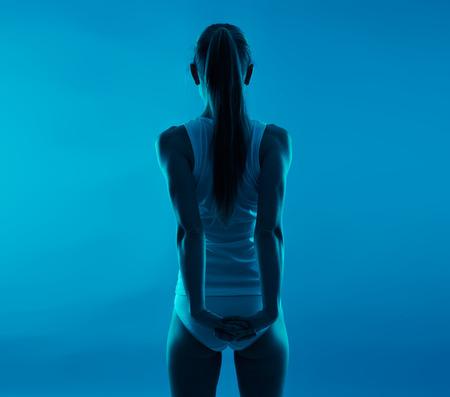 luxacion: rehabilitaci�n cuerpo. Mujer joven que estira los brazos y la espalda sobre el fondo azul.