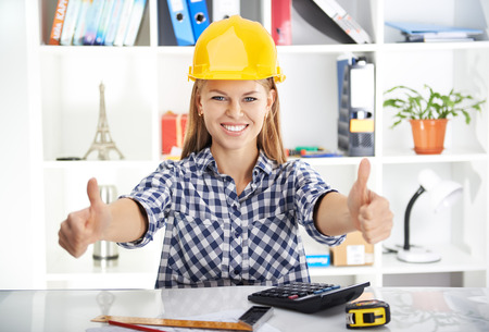 Young prosperous woman engineer in hardhat showing thumbs up at her workplace. Attractive female architect measuring blueprint and calculating business plan. Stock Photo