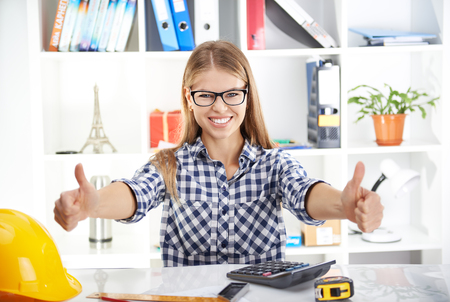 woman engineer: Portrait of happy business woman showing thumbs up in the office. Young successful female designer in eyeglasses calculating project profit. Stock Photo