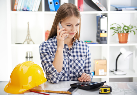 Pretty woman architect making estimate of new construction project. Young businesswoman with phone and draft in the office. Stock Photo