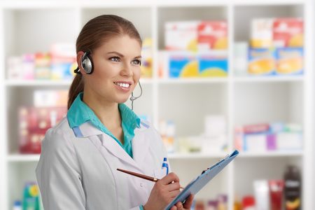druggist: Young woman druggist in headset checking list of pharmaceuticals in warehouse.