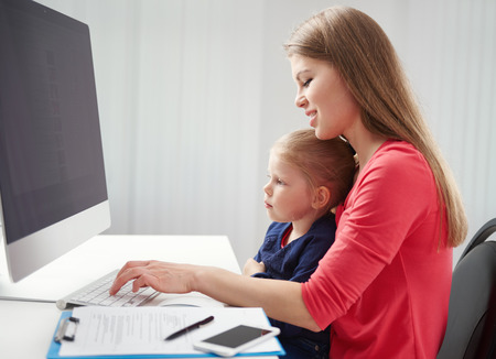 telecommuting: Young businesswoman working at computer with her little daughter in the office. Concept of telecommuting and career.