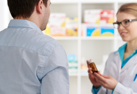 drug store: Male customer buying pills in drug store. Young female pharmacist consulting client, holding medicine bottle.