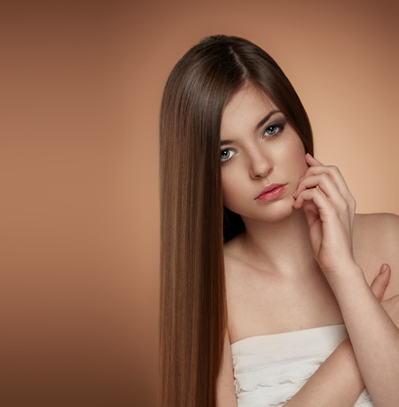 Sensual teenage girl with healthy shiny hair touching her face, looking at camera. Concept of skin and hair care. Stock Photo