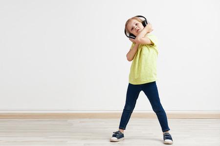 niñas pequeñas: Retrato del estudio de una niña pequeña adorable escuchar música pop en los auriculares. Poco Cutie disfruta de un sonido fuerte.