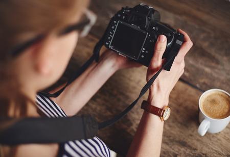 Jonge vrouw fotograaf kijkt naar de camera scherm zitten aan de tafel met een kopje koffie. Concept van de bezetting en levensstijl.