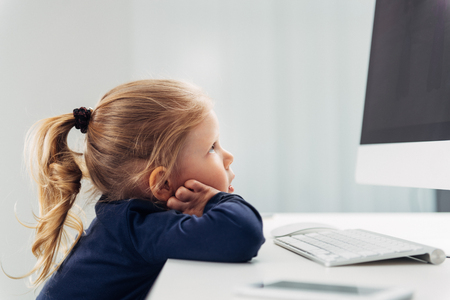 pc monitor: Small concentrated girl looking at monitor, studying pc. Concept of on-line education and application. Stock Photo