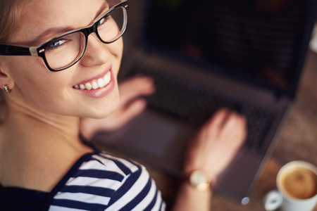 woman work: Close-up of attractive Caucasian female looking at camera, working at computer during breakfast time. Concept of business and technology.