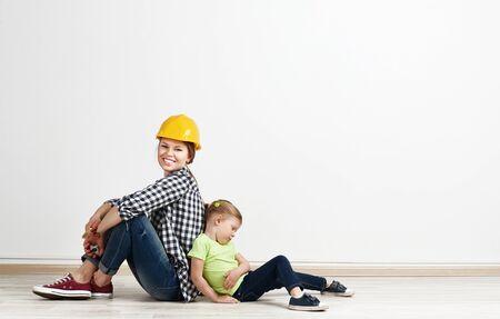 madre trabajando: Retrato de niño cansado y madre sonriente después de la reparación a casa. Concepto de nueva adquisición de vivienda y reubicación.