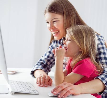 computadora caricatura: Retrato de risa madre y niña viendo la película de dibujos animados en el ordenador. Concepto de actividad de ocio familiar y estilo de vida. Foto de archivo