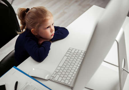 little girl sitting: Adorable little girl sitting at the table looking at monitor in parental office. Concept of e-learning and entertainment. Stock Photo