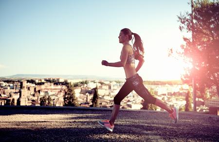 salud y deporte: Ejecución de mujer atlética ejercicio al aire libre al atardecer. Concepto de deporte, fitness y estilo de vida. Foto de archivo