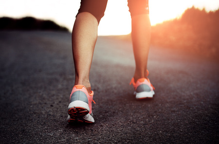 healthy path: Close-up of sportswoman feet in sneakers on the road. Young active female jogger exercising on the trail summer day. Stock Photo