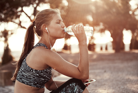 water bottle: Thirsty female jogger drinking fresh water and listening music in headphones after training. Young athletic woman exercising in the park outdoors.